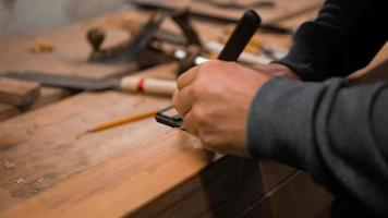 El carpintero marca la pieza de trabajo con un cuadrado y un cuchillo de marcado.