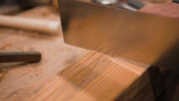 carpintero aserrando una pieza en blanco de madera con una sierra japonesa
