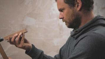 un carpintero barbudo está usando un avión japonés con la ayuda de un mazo