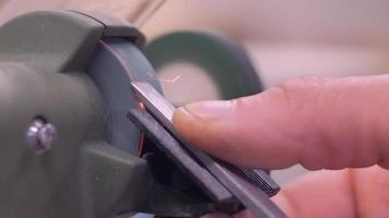 maestro afila el cincel en la máquina de pulir