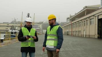Two Working Men Discuss a Project While Standing on a Port video