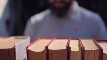um homem turvo folheando livros