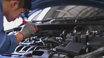 Joven mecánico de automóviles asiático examinando el motor en el capó del coche en el taller de reparación de automóviles. reparador que comprueba el soporte del mantenimiento de seguridad del cliente antes de un viaje largo. concepto de negocio y transporte. video