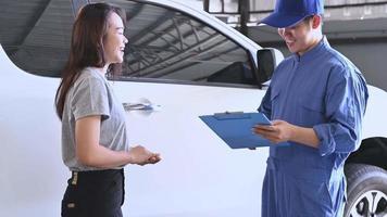 mecánico de automóviles, dar, papeles, a, mujer asiática, para, firmar