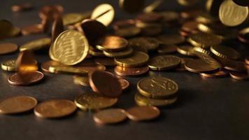 um monte de moedas caindo em uma mesa de madeira