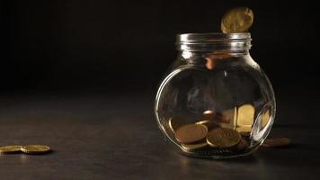 monedas cayendo rápidamente en un frasco de vidrio video