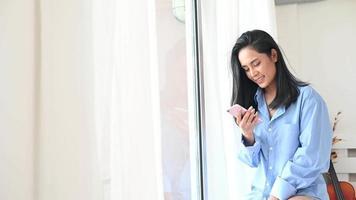 uma mulher ao telefone parada perto da janela
