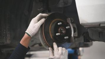 Asian male mechanical examine car disk brake