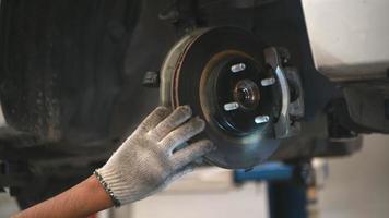 asiatico meccanico tenere una torcia elettrica per esaminare l'auto