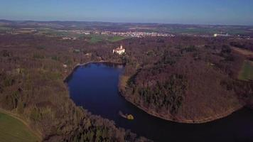 Drone flying over a river towards a castle in 4K