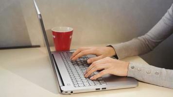 mujer escribiendo en una computadora portátil en la oficina