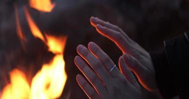 Mano de mujer calentándose sobre el fuego en clima frío