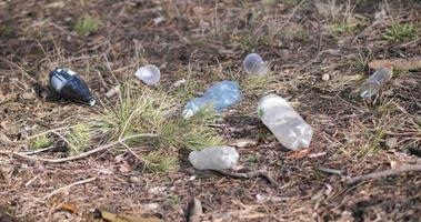 Plastic bottles and other non-degradable waste among grass