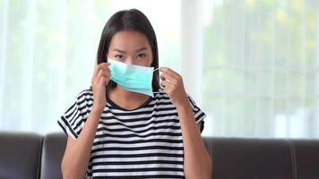 Young Asian woman putting on a mask for protection from coronavirus  video