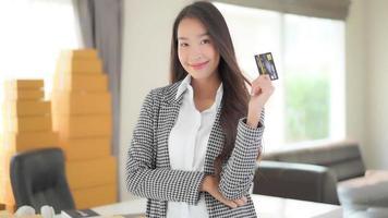 jovem mulher asiática segurando um cartão de crédito video