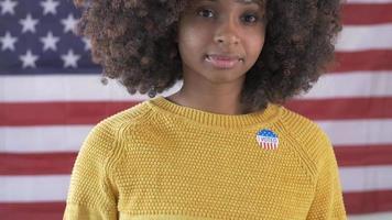 Joven mujer negra votando con bandera americana en el fondo