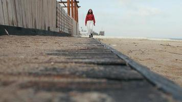 A girl in a red shirt walks on a wooden floor over the sand