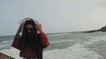 Asian girl in sunglasses by the sea
