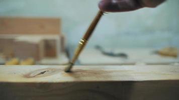una mano extendiendo pegamento sobre un bloque de madera video