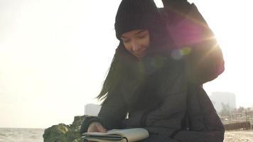 mujer preparándose para escribir sentada en una piedra cerca del mar