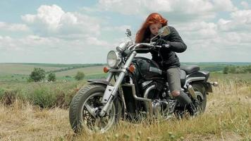 la chica motociclista pelirroja estacionando su motocicleta.