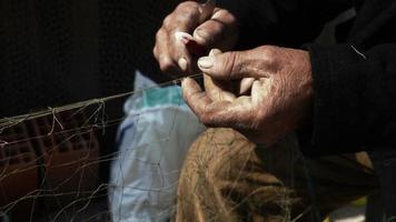 pêcheur répare des lignes de pêche en résille