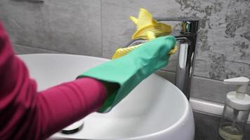 mulher limpa uma torneira com um pano amarelo.