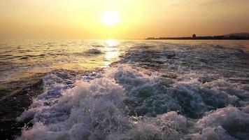 Olas de agua de mar detrás de ferry y puesta de sol
