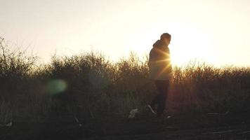 El hombre camina cerca de cruces de piedra al atardecer