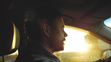 hombre conduciendo un coche al atardecer