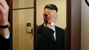 Hombre arreglando su cabello y traje frente a un espejo