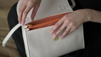 manos de mujer abriendo un bolso
