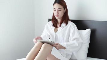 mulher asiática sentada assistindo algo no tablet do computador em casa video