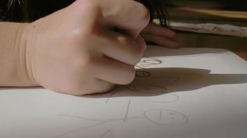 a mão da criança desenha em uma folha de papel
