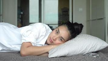 Linda mujer joven durmiendo en la cama despertando y estirando