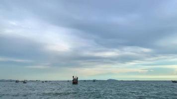 una barca galleggia nel mare la sera con le nuvole