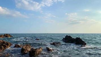 vagues de l'océan échouent sur un rocher avec un ciel bleu