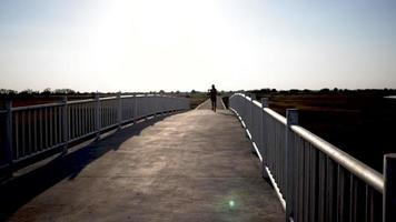 Woman running on the bridge Against Sunlight