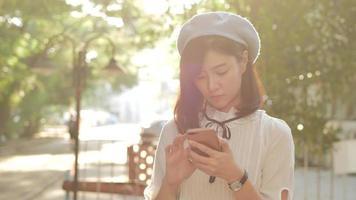 Linda mujer feliz utiliza teléfono móvil en el jardín