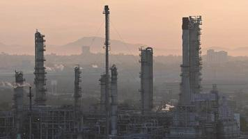 Smoke clouds come out of pipes on refinery factory at sunrise
