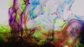 Gotas de color del arco iris en cámara lenta en el agua video