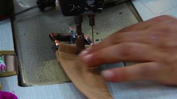 sastre cose un cinturón roto con una máquina de coser