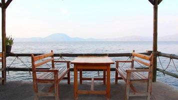 Holztische und Stühle auf der Terrasse mit Meerblick