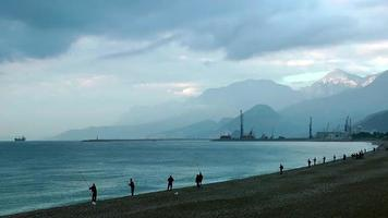 People Silhouette Fishing near the Seaside and Huge Mountains