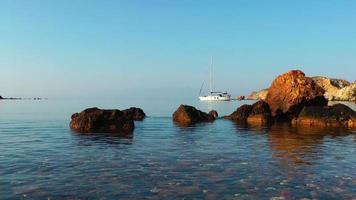 rochas à beira-mar e água do mar pura e um iate video