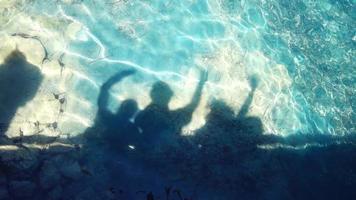 sombras de pessoas na água do mar