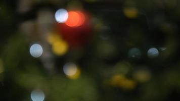 luzes de natal borradas e reflexos dos carros nas vitrines