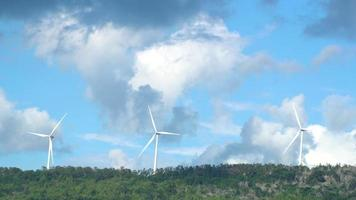 Three wind turbines producing power on mountain video