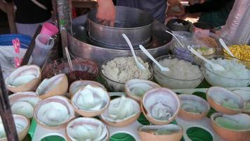 Vendor selling coconut ice cream to customer in Thailand.