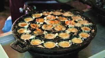 Fried egg with mussels cooking in iron pan video